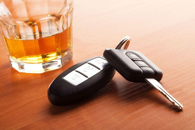 car keys next to glass of alcohol
